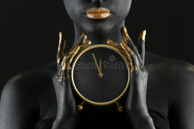 Beautiful woman with black and golden paint on her body holding clock against dark background, closeup royalty free stock photography