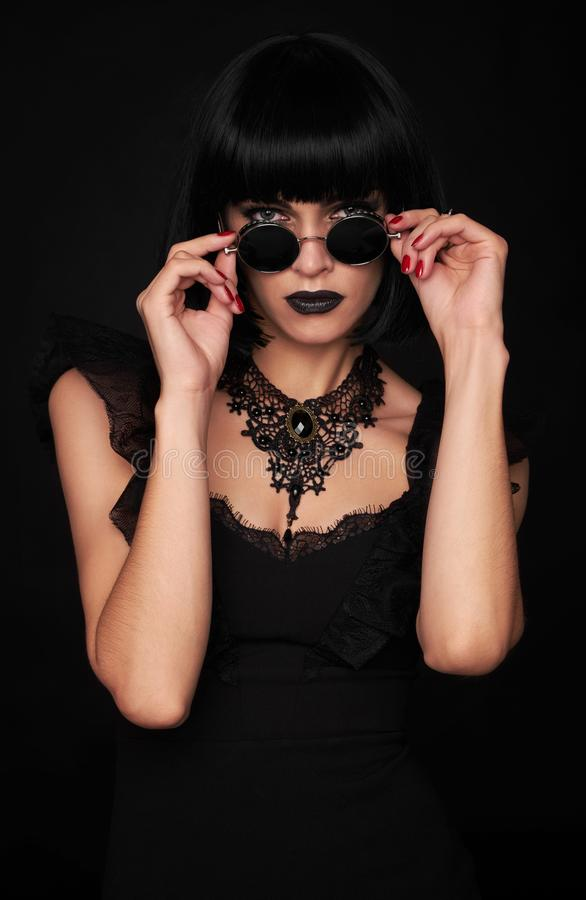 Beautiful woman in black gothic style. Beautiful brunette woman with kare hairstyle and sunglasses in black gothic style. Studio shot royalty free stock photography
