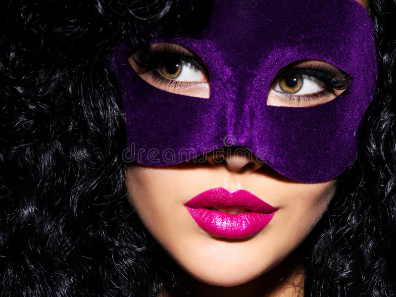 Beautiful woman with black hairs and violet theatre mask on fac. Portrait of a beautiful woman with black hairs and violet theatre mask on face. Purple nails royalty free stock photography