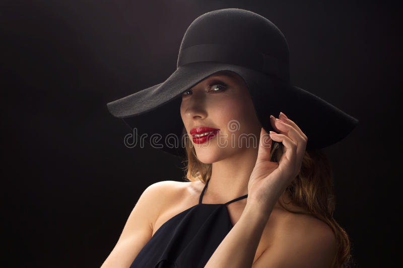 Beautiful woman in black hat over dark background. People, luxury and fashion concept - beautiful woman in black hat over dark background royalty free stock images