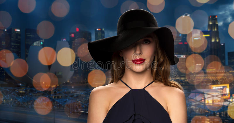 Beautiful woman in black hat over night city. People, luxury and fashion concept - beautiful woman in black hat over night singapore city and lights background stock image