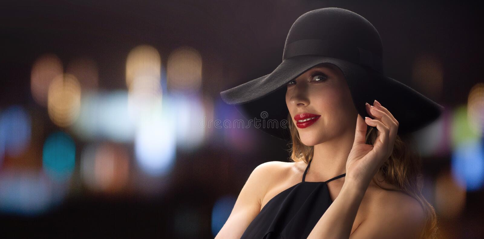 Beautiful woman in black hat over night lights. People, luxury and fashion concept - beautiful woman in black hat over blurred night lights background royalty free stock photography