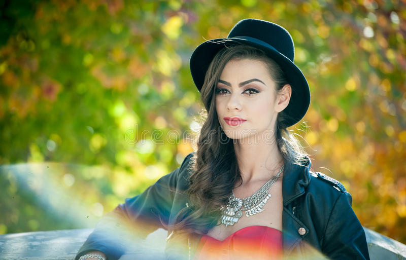 Beautiful woman with black hat posing in autumnal park. Young brunette spending time during autumn in forest. Long hair attractive girl with creative makeup stock photo
