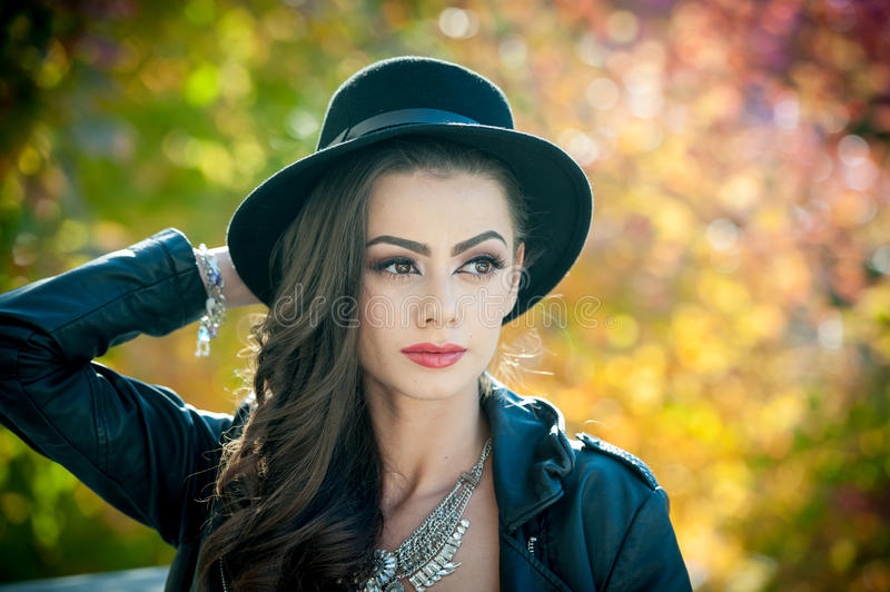 Beautiful woman with black hat posing in autumnal park. Young brunette spending time during autumn in forest. Portrait of long dark hair attractive girl with royalty free stock image