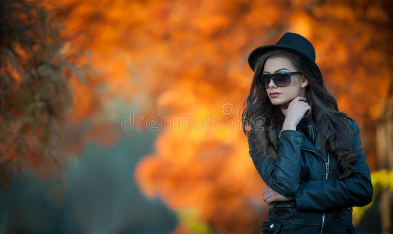 Beautiful woman with black hat and sunglasses posing in autumnal park. Young brunette spending time during autumn in forest. Portrait of attractive girl with royalty free stock photography