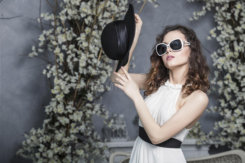 Beautiful woman in a black hat, sunglasses and a white dress on. Background of vintage white spring interior stock photography