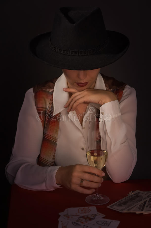 Beautiful woman in a black hat with a wine glass royalty free stock photos