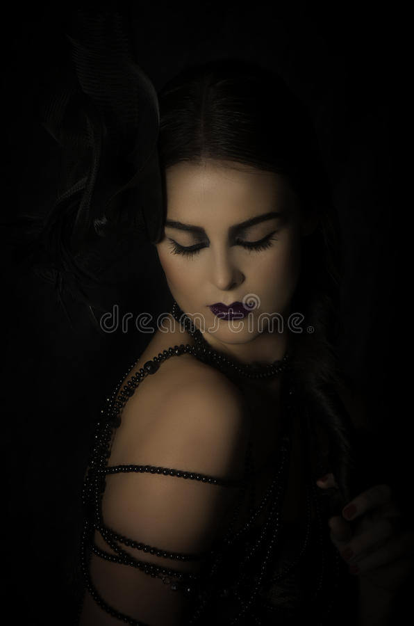 Beautiful woman in black with headdress and beads royalty free stock images