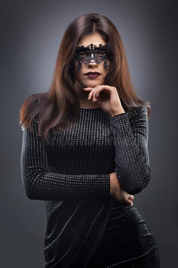 Beautiful woman with black lace mask over her eyes on the dark gray background royalty free stock photos