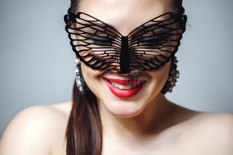 Beautiful Woman with Black Lace mask over her Eyes. Red Lips and Nails closeup. Open Mouth. Manicure and Makeup. Make up concept. Passion. Beautiful female stock image