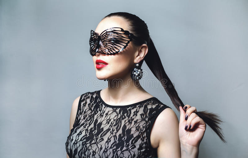 Beautiful Woman with Black Lace mask over her Eyes. Red Lips and Nails closeup. Open Mouth. Manicure and Makeup. Make up concept. Passion. Beautiful female royalty free stock image