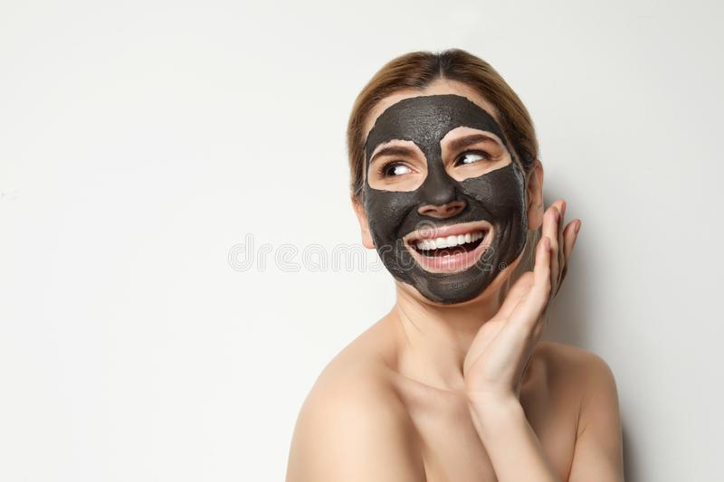 Beautiful woman with black mask on face against light background. Space for text royalty free stock photos