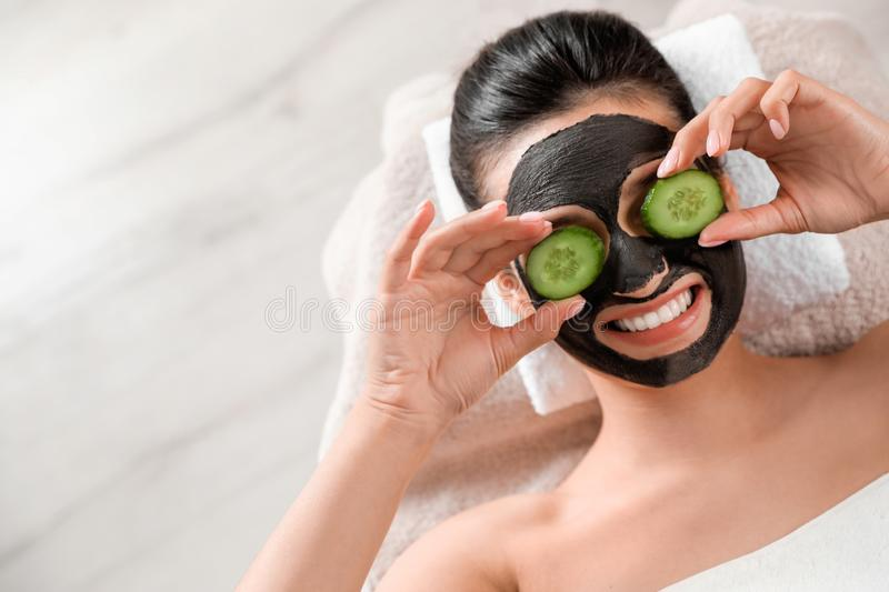 Beautiful woman with black mask on face and cucumber slices relaxing in spa salon. Top view. Space for text stock image