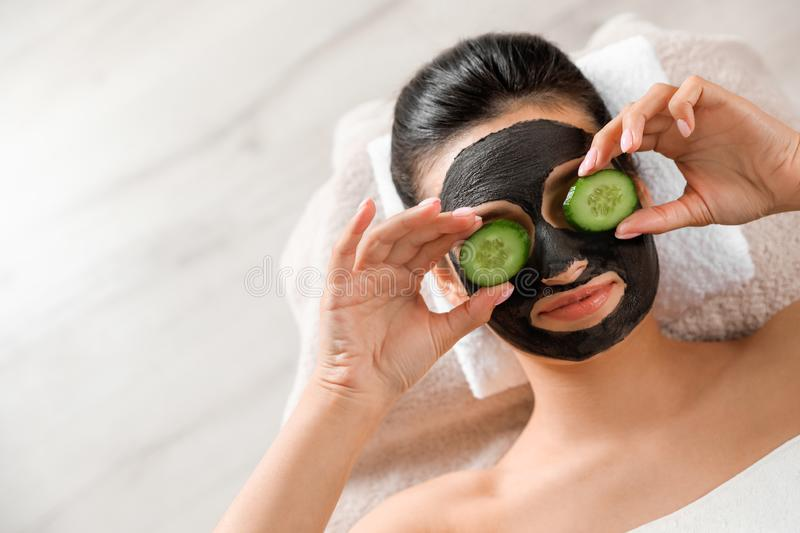 Beautiful woman with black mask on face and cucumber slices relaxing in spa salon, top view. Space for text royalty free stock image