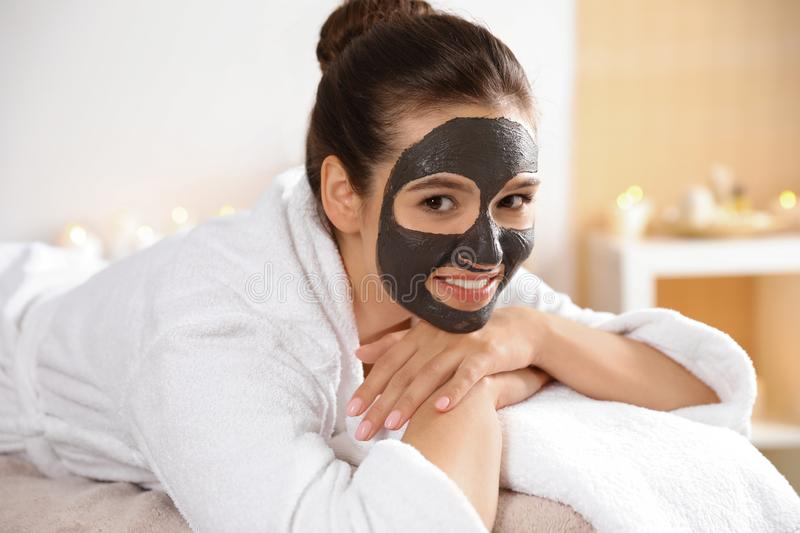 Beautiful woman with black mask on face relaxing. In spa salon royalty free stock image