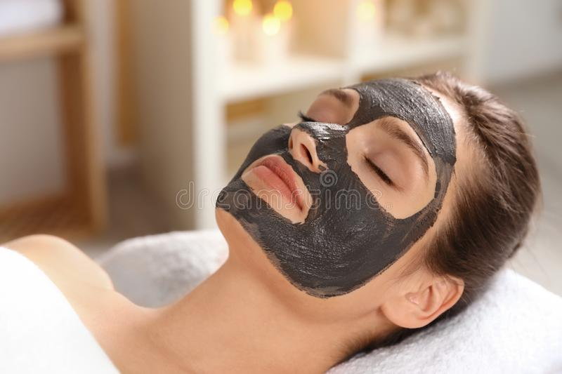 Beautiful woman with black mask on face relaxing. In spa salon stock photo