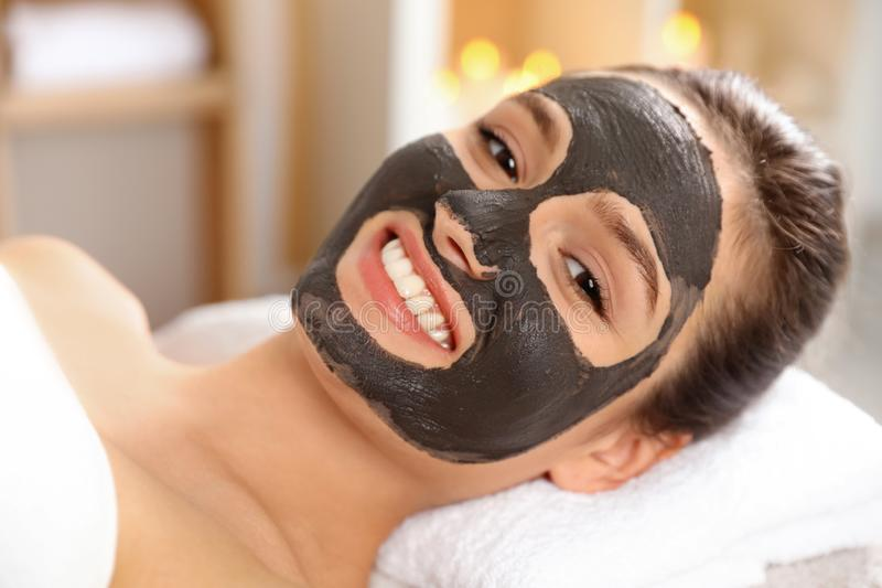 Beautiful woman with black mask on face relaxing. In spa salon stock images