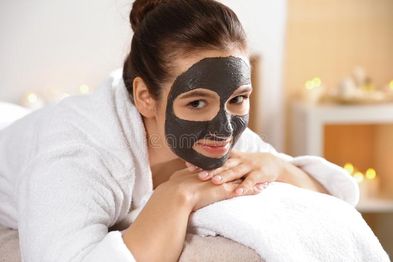 Beautiful woman with black mask on face relaxing. In spa salon royalty free stock images