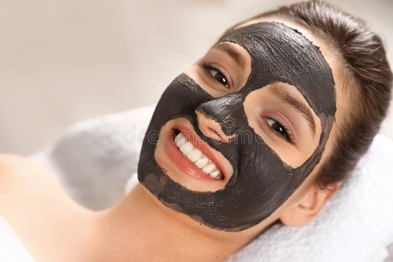 Beautiful woman with black mask on face relaxing in spa salon. Closeup royalty free stock photos