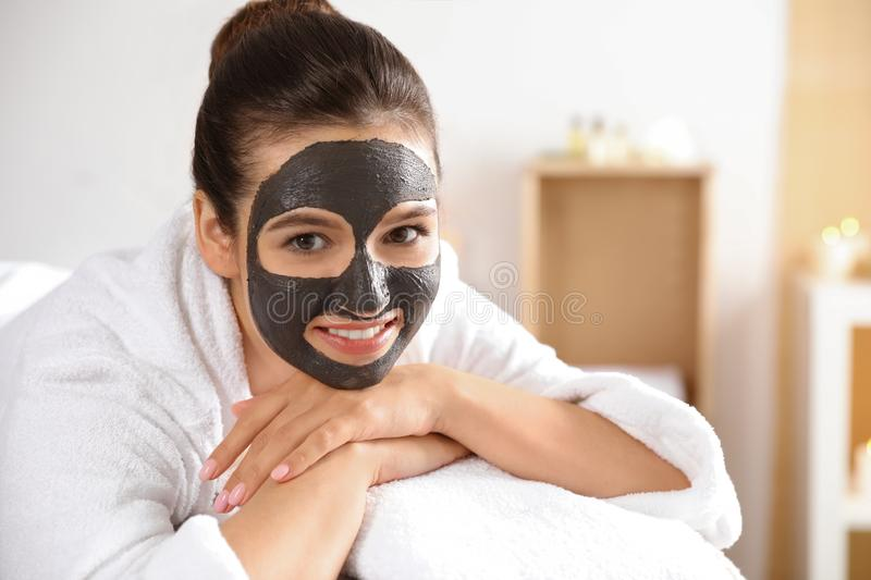 Beautiful woman with black mask on face relaxing in spa salon. Space for text royalty free stock photo