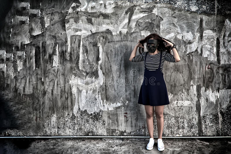 Beautiful woman in black mask standing. In scary abandoned building. Concept of wickedness, sadness, depressed and human problems in dark tone stock photos