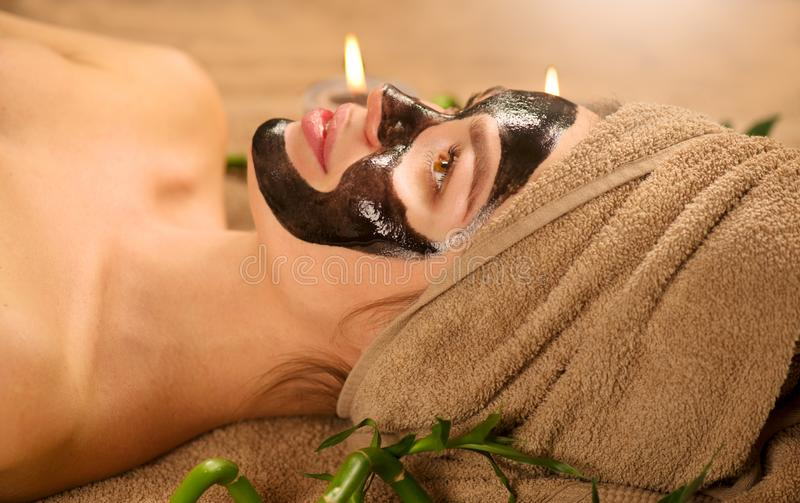 Beautiful woman with black purifying black charcoal mask on her face. Beauty model girl with black facial peel-off mask. Beautiful woman with black purifying royalty free stock image