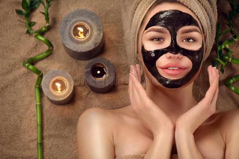Beautiful woman with black purifying black charcoal mask on her face. Beauty model girl with black facial peel-off mask. Lying in spa salon. Skin care, acne stock images