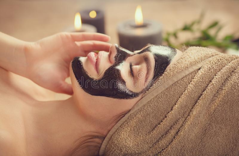 Beautiful woman with black purifying black mask on her face. Beauty model girl with black facial peel-off mask lying in spa salon. Skin care, acne treatment stock photos