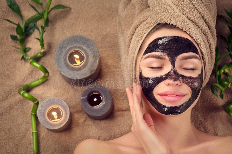 Beautiful woman with black purifying black charcoal mask on her face. Beauty model girl with black facial peel-off mask royalty free stock images
