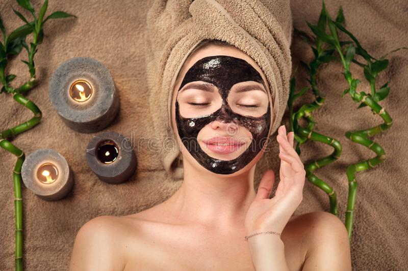 Beautiful woman with black purifying black charcoal mask on her face. Beauty model girl with black facial peel-off mask royalty free stock photography