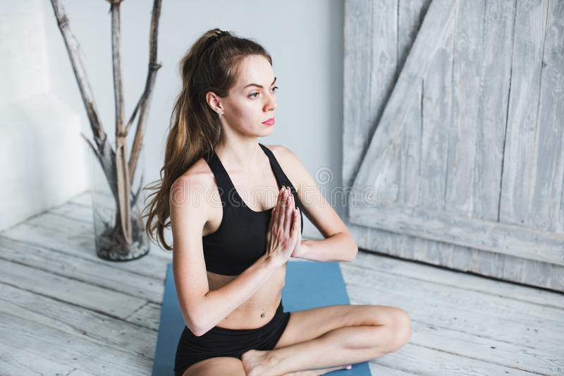 Beautiful woman in black sportswear in the lotus position stock photography