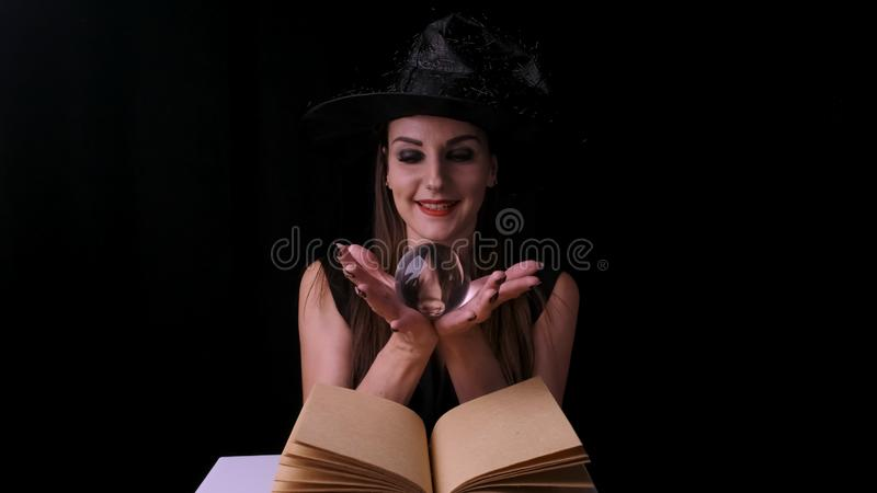 Beautiful woman in a black witch costume and hat, holds a transparent magic ball in her hands and conjures. Halloween royalty free stock image