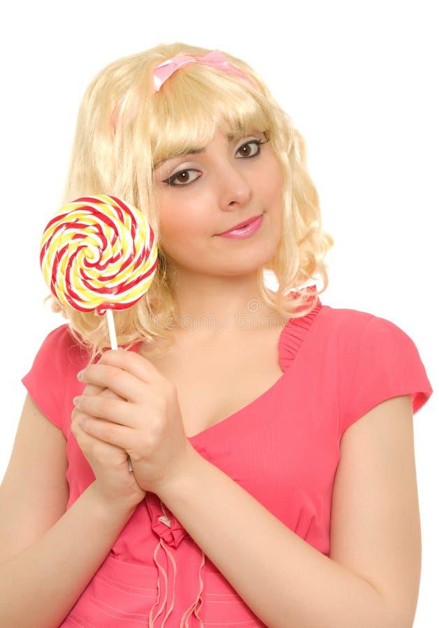 Beautiful woman in blond wig with lollipop