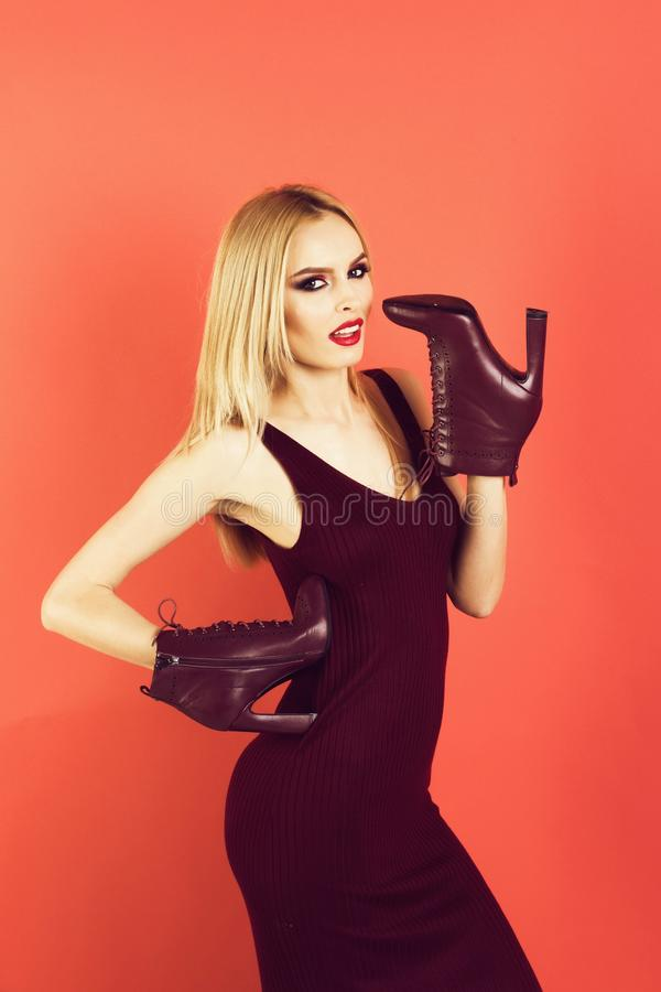 Beautiful woman with blonde hair, makeup, holds leather shoes. Sensual glamour portrait of beautiful woman model with makeup has red lips color and clean healthy royalty free stock photography