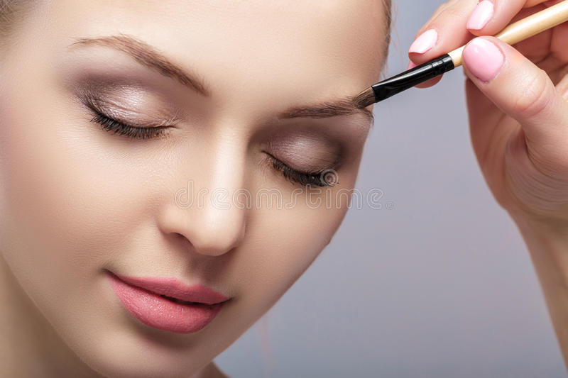 Beautiful woman blonde uses professional brush for eyebrow makeup. Close up royalty free stock photography