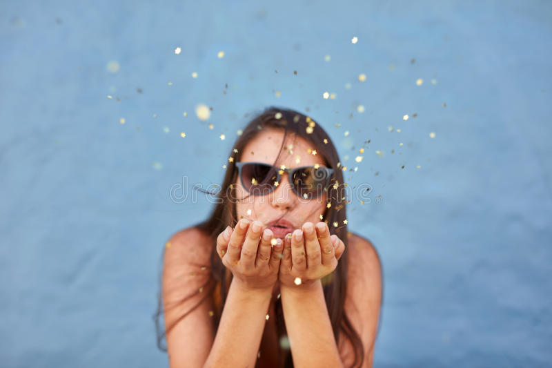 Beautiful woman blowing a burst of magic glitter stock photography