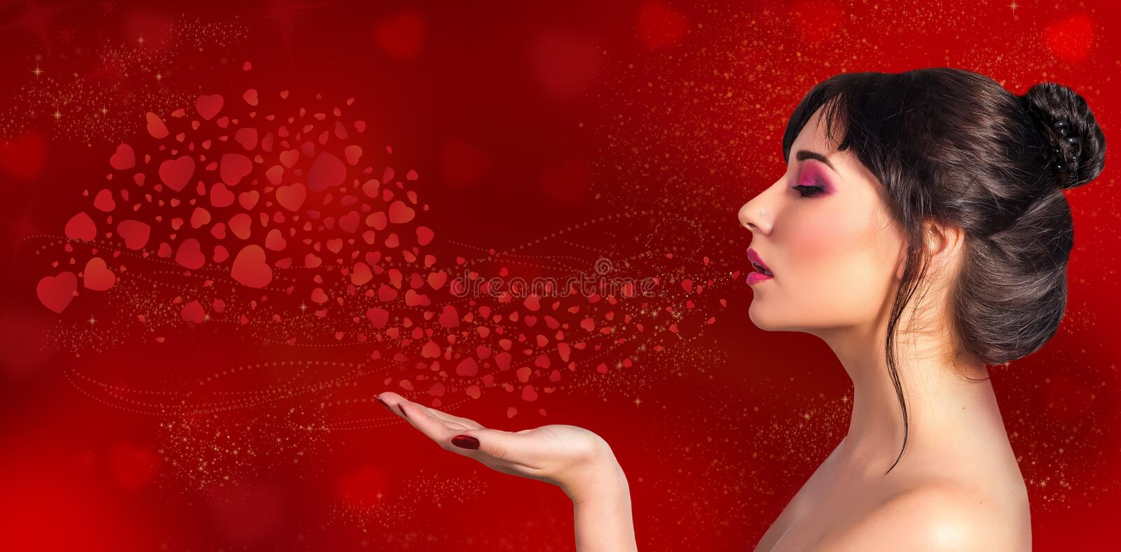 A beautiful woman blows on her hand and red hearts fly on a holiday red background. Composition to Valentine Day, girl on red background with a copy space stock image