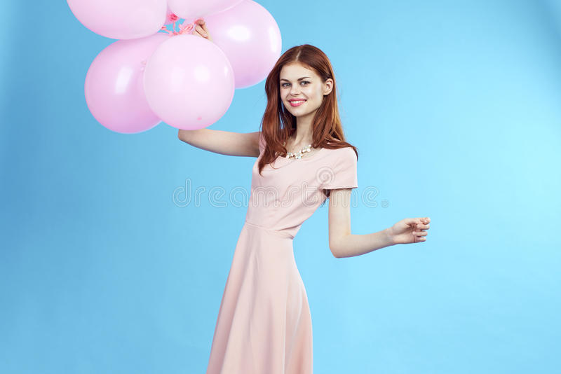 Beautiful woman on a blue background in a dress holding balloons, smile, blank space for copy stock image