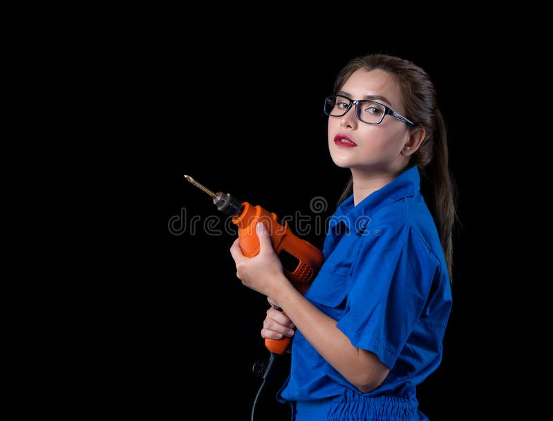 A beautiful woman in the blue dress shirt holds a drill used in the construction. Of a studio with a black background, adult, asian, beauty, builder, building stock photo