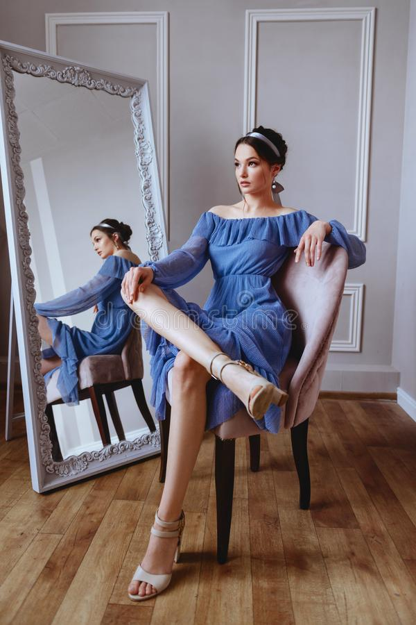 A beautiful woman in a blue dress is sitting on a velvet armchair stock photos