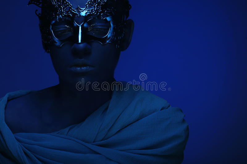 Beautiful woman with blue face with mask stock photography
