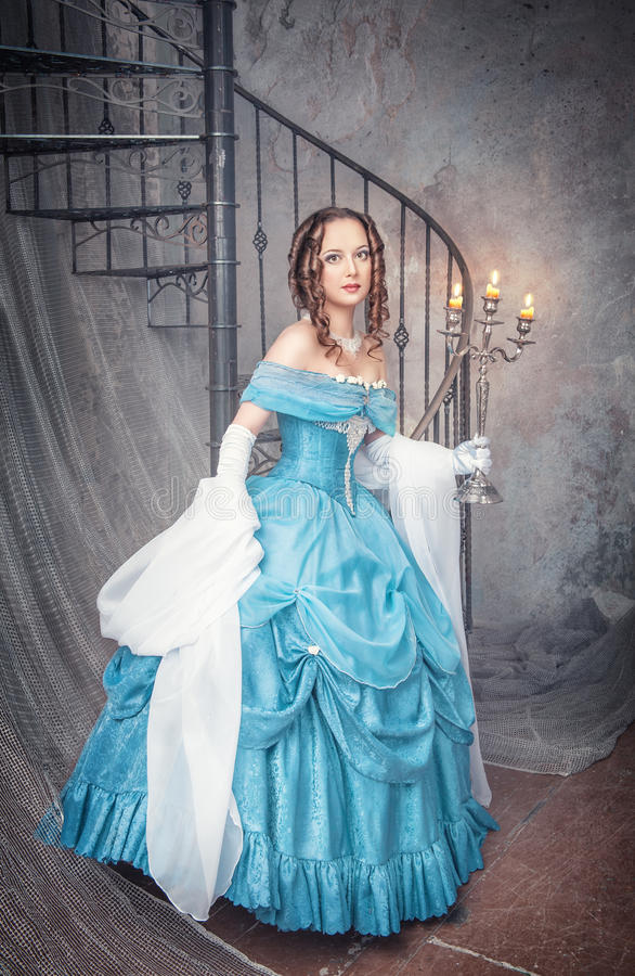 Beautiful woman in blue medieval dress with candelabrum royalty free stock images