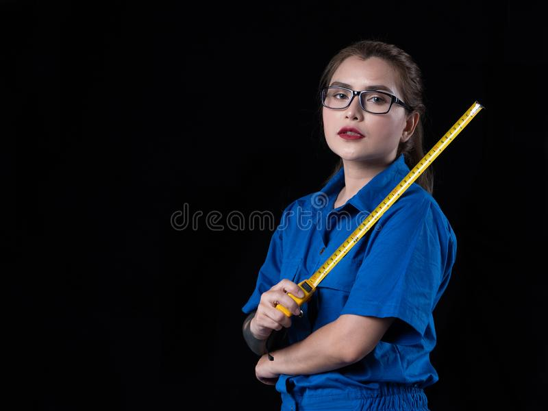 A beautiful woman in the blue technician uniform holding a construction tool. In a studio with a black background, action, adult, asian, beauty, builder royalty free stock photos
