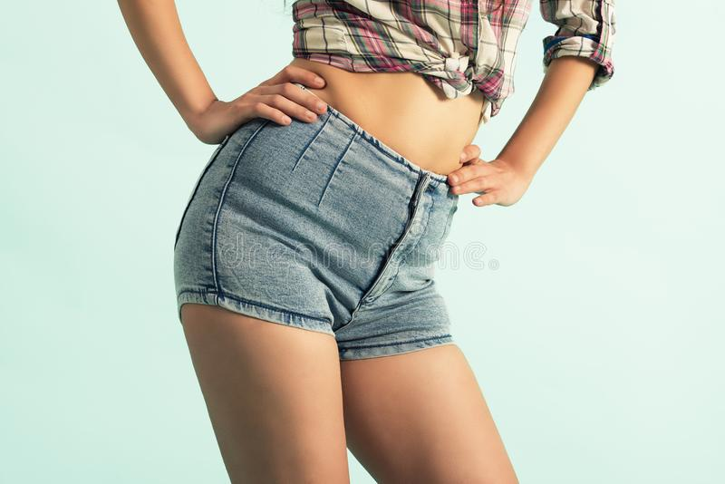 Beautiful woman body in denim jeans shorts on green background stock photography