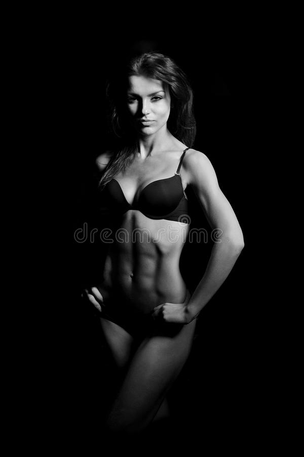 Beautiful woman bodybuilder. Posing in black bikini on black background stock images
