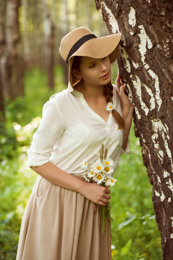 Beautiful woman with a bouquet of daisies near birch stock images