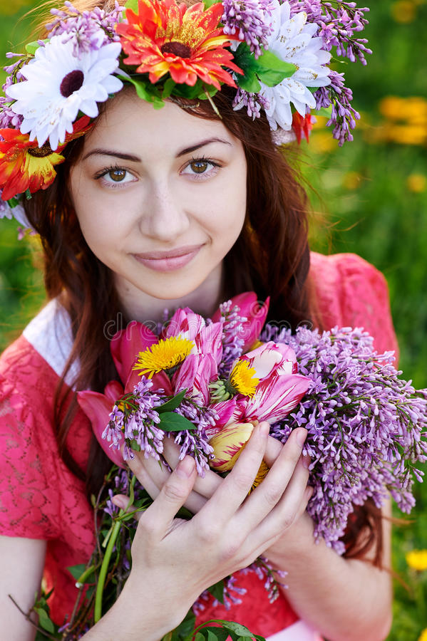 Beautiful woman with a bouquet of lilac in a wreath royalty free stock photos