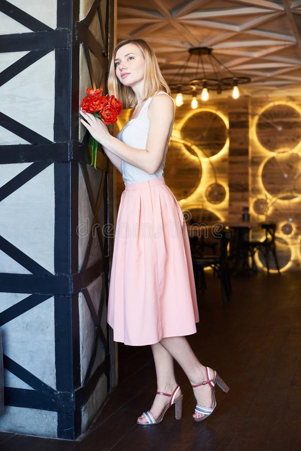 Lovely girl dreamily looks and holds flowers in her hands in the cafe stock images
