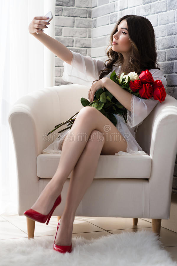 Beautiful woman with bouquet roses makes selfie. In studio stock image