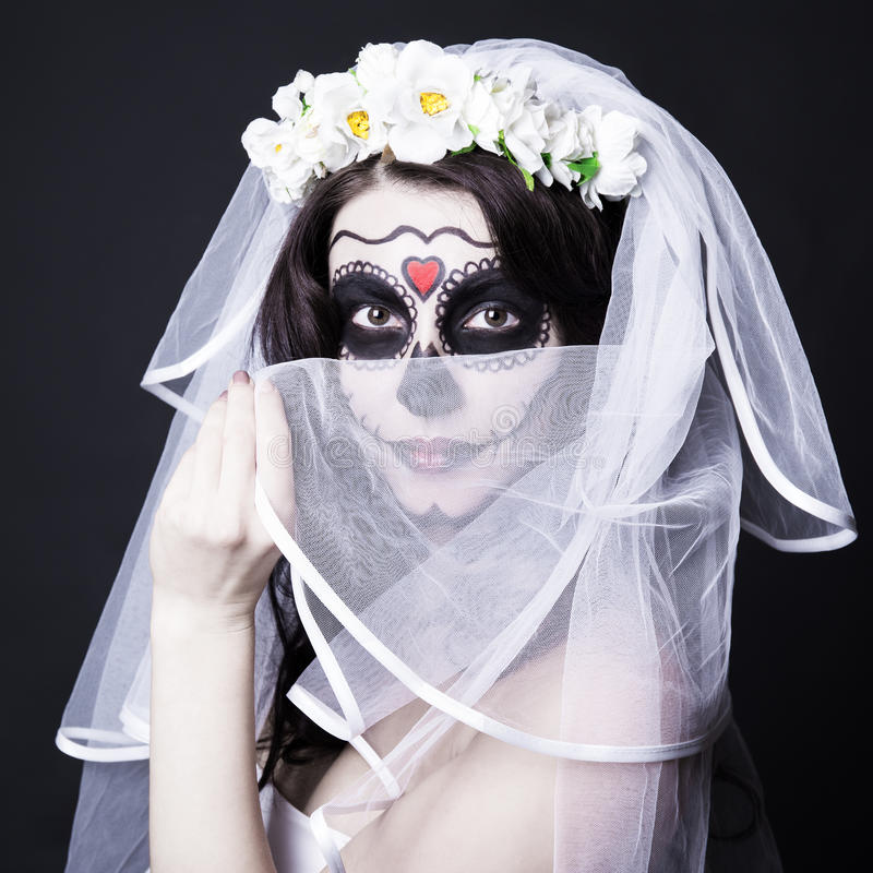 Beautiful woman bride with creative sugar skull make up and bridal veil over black. Background royalty free stock image